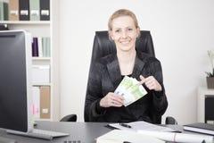 Gerente feliz en su escritorio que sostiene una fan del efectivo imagen de archivo libre de regalías