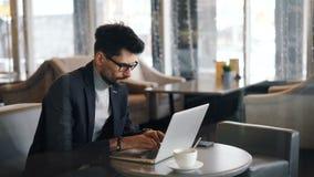 Gerente incorporado que trabalha no café durante a pausa para o almoço usando o portátil moderno video estoque