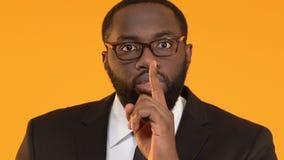 Gerente masculino preto que mostra o gesto do silêncio, segurança da informação, ruptura dos dados filme