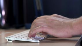 Gerente masculino que datilografa no teclado no escritório na noite Um relógio esperto é vestido na mão Close-up vídeos de arquivo