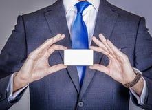 Gerente no terno que guarda um cartão Imagens de Stock Royalty Free
