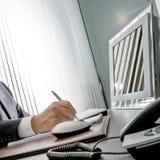 Gerente no trabalho A mão perita de um homem de negócios que senta-se em sua mesa, guarda a pena na frente de seu monitor do comp imagem de stock royalty free