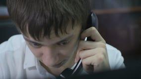 Gerente novo Takes Handset do close up na frente do monitor filme