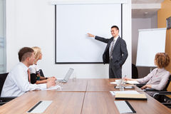 Gerente que apresenta o whiteboard a seus colegas Imagens de Stock Royalty Free