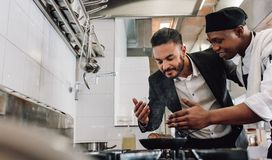 Gerente que cheira o aroma do alimento com cozinheiro chefe fotos de stock royalty free