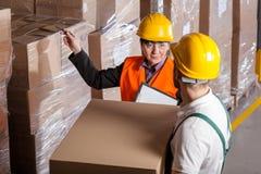 Gerente que dá a instrução do trabalhador no armazém Fotografia de Stock Royalty Free