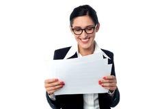 Gerente que olha smilingly relatórios comerciais Foto de Stock Royalty Free