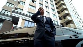 Gerente sério que fala no telefone, estando pelo carro, acionista de espera, esforço imagens de stock