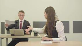 Gerente seguro da mulher do retrato no vestuário formal que senta-se na mesa no primeiro plano que toma documentos de filme