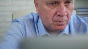Gerente seguro que trabalha no portátil no escritório que alcança a informação financeira video estoque