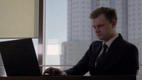 Gerente superior do homem em um terno de negócio em seu local de trabalho no computador no escritório filme