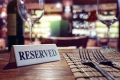 Gereserveerd teken op restaurantlijst met barachtergrond stock fotografie