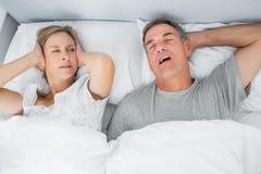 Geërgerde vrouw die haar oren van lawaai van echtgenoot het snurken blokkeren Royalty-vrije Stock Afbeeldingen
