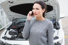 Geërgerde vrouw op de telefoon naast haar opgesplitste auto Royalty-vrije Stock Foto