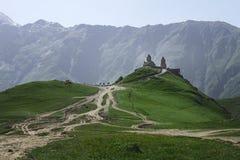 Gergeti三位一体的领港教会在山的在乔治亚在山背景的夏天在与pic的绿草 免版税库存照片