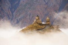 Gergeti kyrka i dimma Arkivbild