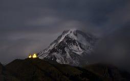 Gergeti kyrka på bakgrund av den monteringsKazbek natten Arkivbild