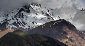 Gergeti Treenighetkloster på en bakgrund av snö-korkade Kaukasus berg och moln, skott i Kazbegi Arkivfoto