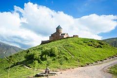 Gergeti Treenighetkyrka, Tsminda Sameba på kullen nära det Kazbek berget i Georgia arkivfoton