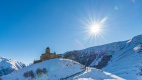 Gergeti Trinity Church and the afternoon sun, Kazbegi, Georgia. Gergeti Trinity Church is located near the village of Gergeti in Georgia. The church is situated Royalty Free Stock Image
