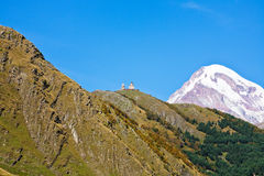 Gergeti Trinity Church and Mount Kazbek in Georgia Stock Photography