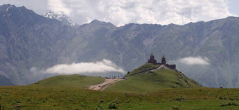 Gergeti Trinity Church. Panoramic photo of famous and popular between tourists place in Georgia. Gergeti Trinity Church is historical church in beautiful Stock Photo