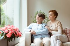 Geriatric woman and her professional caretaker sitting on a couc. Geriatric women and her professional caretaker sitting on a couch and looking through a window royalty free stock photography