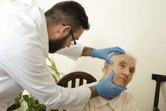 Geriatrician доктора во время доктора испытания рассматривает изменения в коже старухи Стоковое фото RF