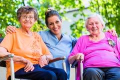 Geriatrische verpleegster die praatje met hogere vrouwen hebben Royalty-vrije Stock Afbeelding