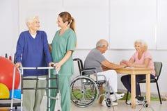 Geriatrisk sjuksköterska med gruppen av högt folk royaltyfri fotografi