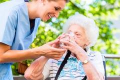 Geriatrisk sjuksköterska som ger exponeringsglas av vatten till den höga kvinnan arkivfoton