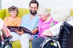Geriatryczna pielęgniarka patrzeje obrazki z seniorami fotografia royalty free
