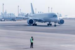 Geriebene Mannschaft handhaben die Bewegung des Flugzeuges am Flughafen stockbild