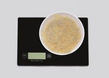 Geriebener Käse auf einer digitalen weißen Küchenskala (produc wiegend lizenzfreie stockfotos