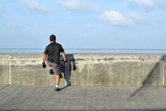 Gerijpte mens die uitrekkende oefening langs het oceaanwater van de baaionderbreking doen stock foto's
