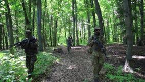 Gerillasoldatkrigaretrupp som går i ett bildande som bär deras vapen stock video