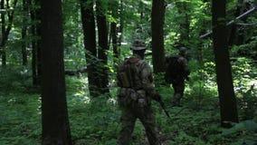Gerillasoldatkrigaretrupp som går i linjen bildande som bär deras vapen i skogbuskarna arkivfilmer