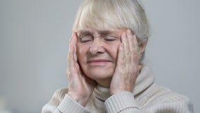 Gerimpeld hoger wijfje die aan sterke hoofdpijn lijden, die tempels, gezondheidszorg masseren stock footage