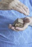 Gerimpelde handen die een klein blokhuis houden royalty-vrije stock foto
