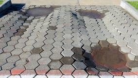Geringe Qualität von Straßenarbeiten - Gruben mit Wasser auf dem Bürgersteig ausgebreitet von den neuen Fliesen lizenzfreies stockfoto