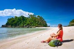 Gerl joven con la mochila que se relaja en costa y que mira a un isla Imagen de archivo