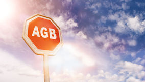 German AGB Terms on red traffic road stop sign. AGB German abbreviation for Terms and Conditions on red traffic road stop sign in front of blue sky with clouds Royalty Free Stock Photos