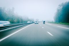 German autobahn highway blurred motion with white car and motorc. Yclist driving on cold day Stock Photography