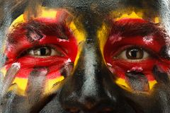 Eyes of German or Belgian sports fan patriot. Painted country flag on man face. Royalty Free Stock Photos
