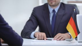 German boss signing employment contract with immigrant employee, shaking hand. Stock footage stock footage