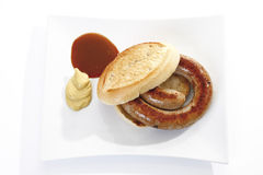 German Bratwurst, fried sausage and bread roll on plate Stock Images