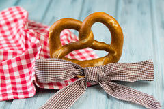 German bretzel and checkered bow on wooden background. German bretzel and checkered bow on a light blue wooden background Royalty Free Stock Image