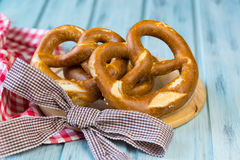 German bretzels on wooden background. German bretzels and checkered napkin on a light blue wooden background Royalty Free Stock Photos
