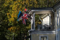 German, British, Estonian and American flags waving in the wind on the old house royalty free stock photo