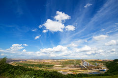 German brown coal surface mining landscape with cloudy blue sky Stock Photos
